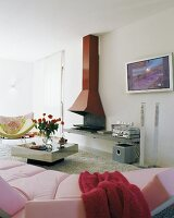 View across pink sofa of open fireplace with red chimney breast in modern living room