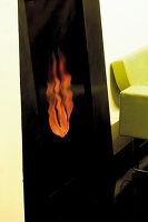 Picture of flames and corner of lime green designer sofa in living room