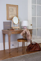 Antique-style dressing table and delicate brass chair in elegant bedroom