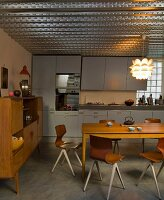 Modern, retro chairs and simple wooden table in open-plan kitchen with fifties charm