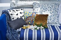 Blue and white striped couch with colourful, patterned scatter cushions in front of Baroque wall-mounted mirrors