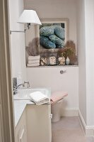 Classic bathroom with marble washstand and seashell arrangements on shelf below framed picture