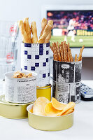 Snacks in tin cans decorated with newspaper
