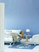 Bedside table and modern armchair in front of blue-painted wall