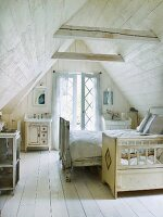 Wood-panelled attic bedroom with cot and double bed