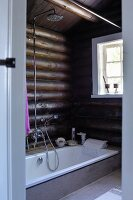 Modern bathroom in log cabin - sunken bathtub against log walls
