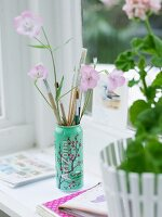 Paintbrushes in can next to potted plant on windowsill