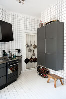 Black and white designer kitchen - black cupboards on walls tiled from floor to ceiling and white wooden floor
