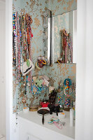 Open jewellery racks hanging over dressing table on bedroom wall with wallpaper patterned with gold floral design