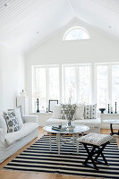 Pale attic interior with white sofa set and Oriental side table on black and white rug