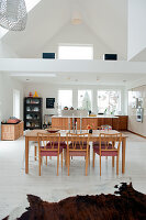 50s-style wooden dining table and chairs in front of kitchen area and view into mezzanine in open-plan house