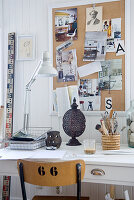 Desk lamp on desk below pinboard on white wooden wall