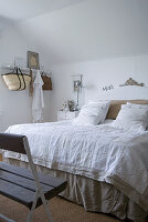 Double bed with linen bed covers in bedroom with rustic wooden bench and white hook rack on wall
