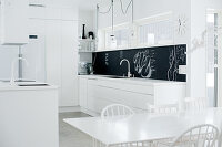 Open-plan designer kitchen in purist white with black splashback