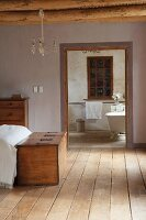 Chest at foot of bed and view into simple bathroom through open doorway