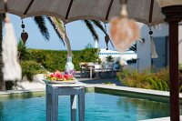 Sunny day beside the pool with refreshing fruit platter on stool