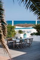 Idyllic terrace complex with set table, comfortable benches and sea view