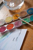 Paintbox and paint brush next to glass of water on table