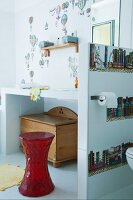 Modern bathroom with red stool in front of masonry washstand against white-tiled wall with hot-air balloon motifs