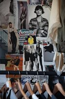 Wooden coathangers on clothes rail in front of wall decorated with photos cut from magazines