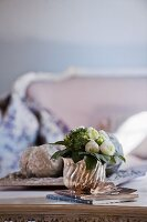 White ranunculus in silver pot on coffee table