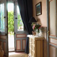 An anteroom with a view through an open front door of a traditional Mediterranean country house in soft pink and blue tones