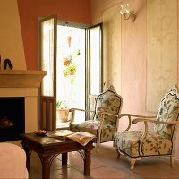 Two antique-style armchairs with floral upholstery in front of fireplace and open terrace door