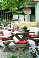 Rustic seating area with wooden benches, wooden table and cushions in front of stable
