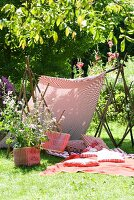 Cushions and picnic blanket in garden beneath awning made from length of fabric