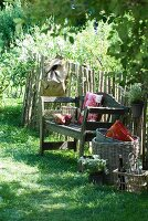Rustic seating area in garden: old wooden bench with scatter cushions, backpack, wicker basket, basket of bottles