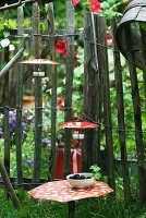 Tealight holders with red metal lids as decoration in cottage garden