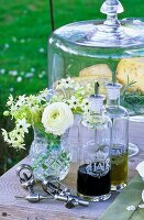 Vinegar, oil, corkscrew, bouquet of flowers and cheese on a garden table