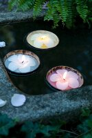 Flower-shaped candles in floating coconut shells