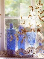 Blue glass vases behind a transparent tulle curtain with floral embroidery