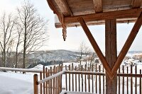 Detail of wooden fence, wooden support and rustic roof structure in snowy mountain landscape