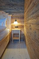 Bedside table with lit lamp in bedroom of wooden hut