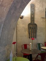View through arched doorway of bistro tables with colourful chairs and oversized fork as wall decoration