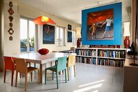 Modern dining table and chairs of various colours in front of large picture above books on sideboard against blue partition