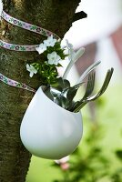 Cutlery in pot hanging on tree trunk