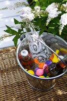 Decorative drinks bottles cooling amongst colourful balloon ice cubes in metal bucket; white flowers in background