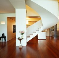 Free-standing staircase in open-plan interior with reddish parquet floor