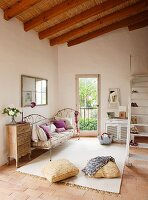 Mediterranean ambiance in simple interior with thatched panels on ceiling; delicate metal couch and vintage chest of drawers combined with pale rug on terracotta floor