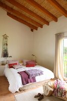 Exposed roof structure with straw mats in pleasant, bright bedroom; red and purple cushions and blankets on French bed