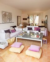 Cushions in shades of purple on white sofas in bright, open-plan living-dining room with terracotta floor