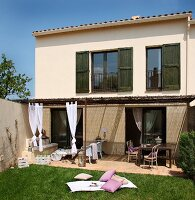 Simple Spanish holiday home with dark green shutters and straw-thatched pergola with draped curtains above furnished terrace