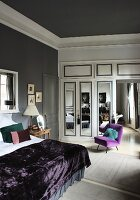 Double bed with purple bedspread, chair with purple upholstery and white fitted wardrobe with mirrored doors in bedroom with grey walls