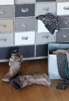 Ladies' boots on wooden floor in front of vintage chest of drawers with clothing spilling from open drawer