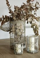 Dried branches of leaves in vintage-style bird cage and white candles in candle lanterns