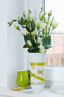 White Texas bluebells (Eustoma grandiflorum) in vase decorated with green masking tape; lime green china jug in background