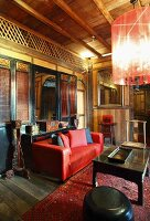 Oriental lounge with wooden lattice walls, red leather couch and black coffee table on rug